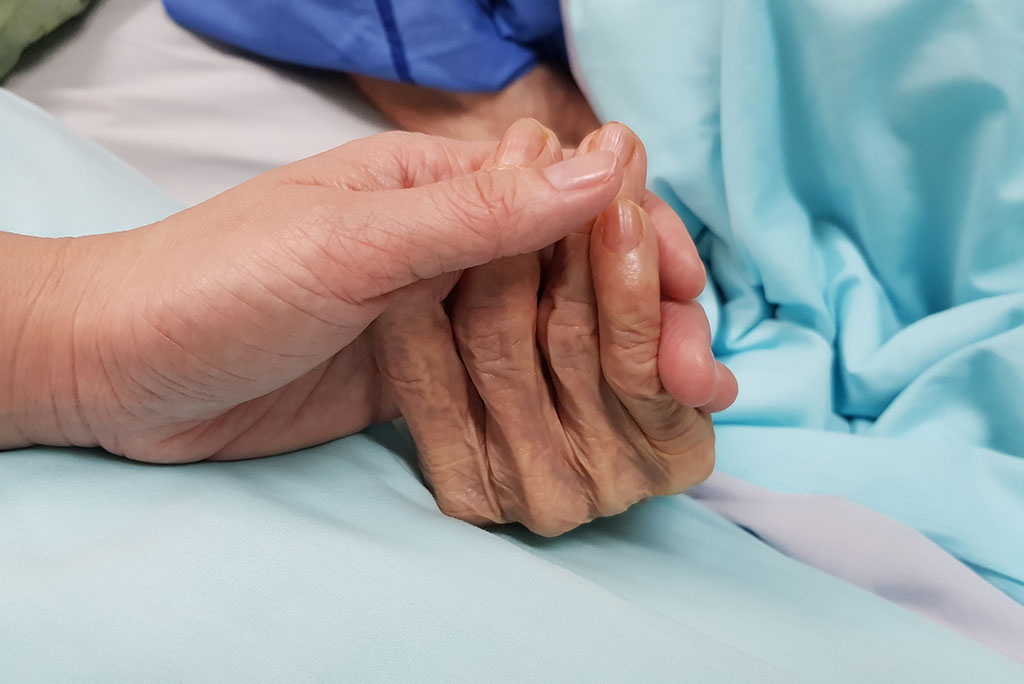 End of life care holding hands